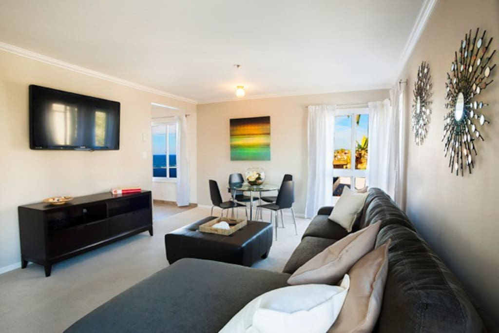 Ocean view living room with 52 inch flat screen TV and seating for 5 guests.