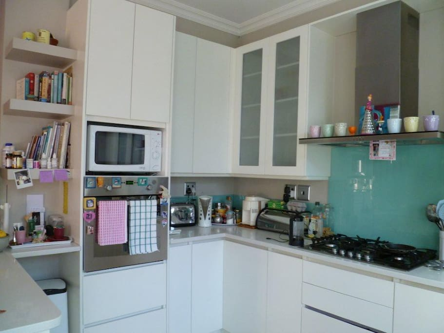 Fitted kitchen with gas hob, oven, microwave, coffee machine and juice extractor