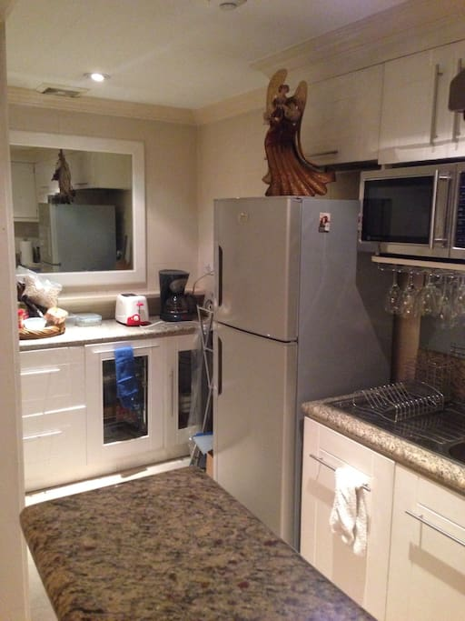 The kitchen features a refrigerator, microwave oven, convection range, sink and drip coffee maker.
