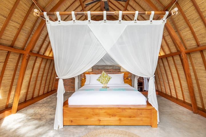 Cozy queen sized bed in the first floor right under the arched natural grass roof.