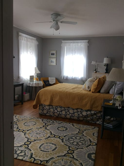 """""""The Grey Room"""" is a private room with a queen bed, TV, table, and fan."""
