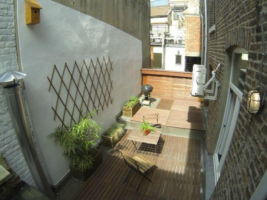 Terrasse privée avec table, chaise et barbecue