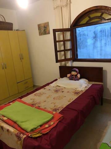 Quarto com uma cama de solteiro ,  uma de casal e ventilador de teto.