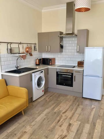 Kitchen area with washer/dryer, microwave, toaster, Fridge/freezer cookware, utensils and crockery.
