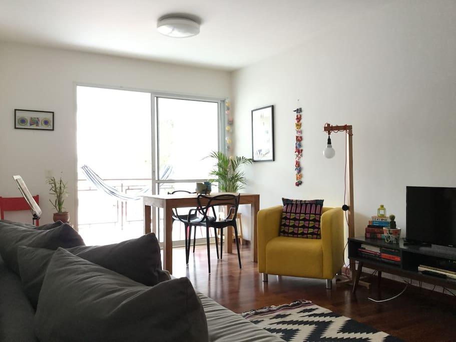 """This is our sunny living and dining room equipped with a comfortable sofabed, TV, table, many books and a balcony with a """"rede"""""""