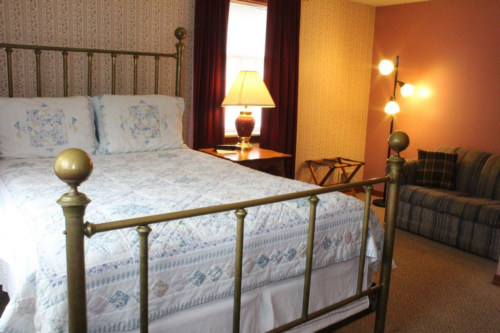 Master Bedroom with a queen size bed, sitting area, and 2 small camp beds for children