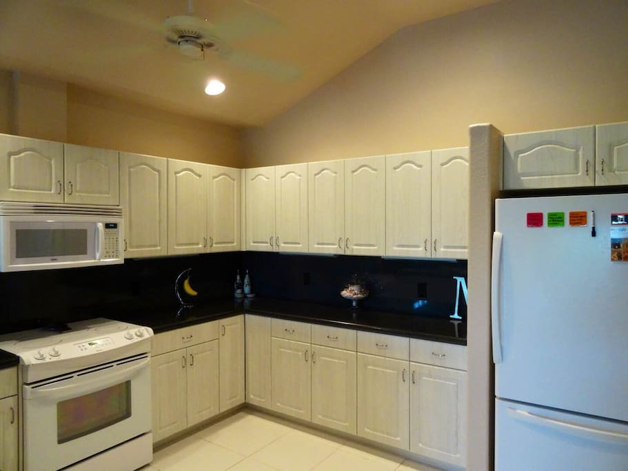 Kitchen furnished with refrigerator, oven, microwave, dishwasher, coffeemaker, dishes, eating and cooking utensils