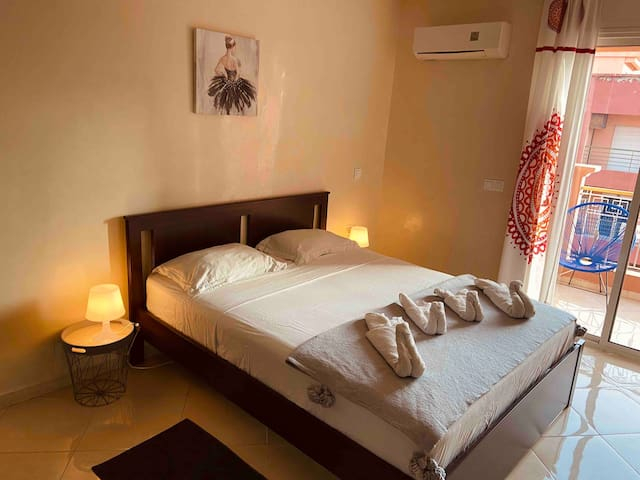 Chambre avec lit Queen size 160x200, rangements, miroir, balcon et climatisation.