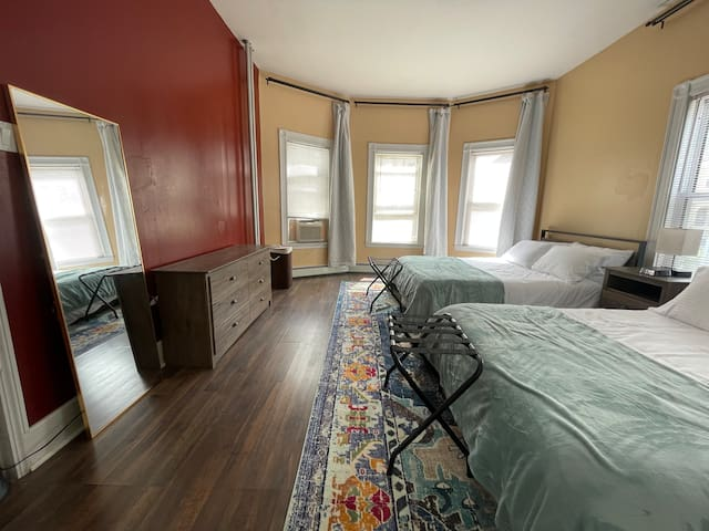 Bedroom with double queen beds, blackout curtains, dresser, large closet