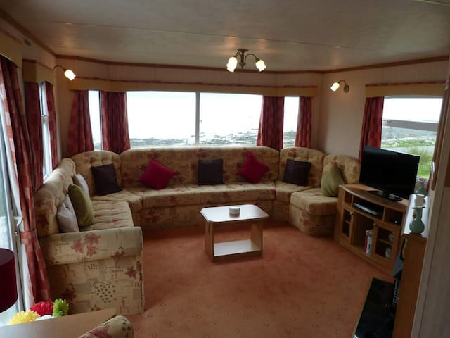 Wrap around sofa has room for everyone. Fab sea views from the window.