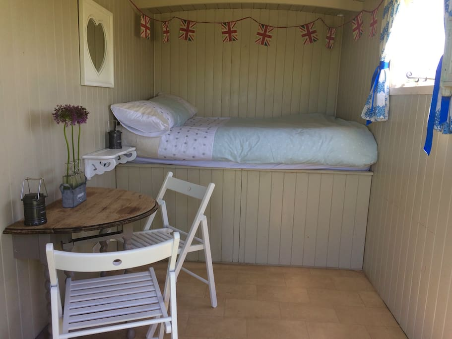 Inside our hut, double bed complete with bedlinen, fold away table and chairs, led lanterns and plenty of storage.