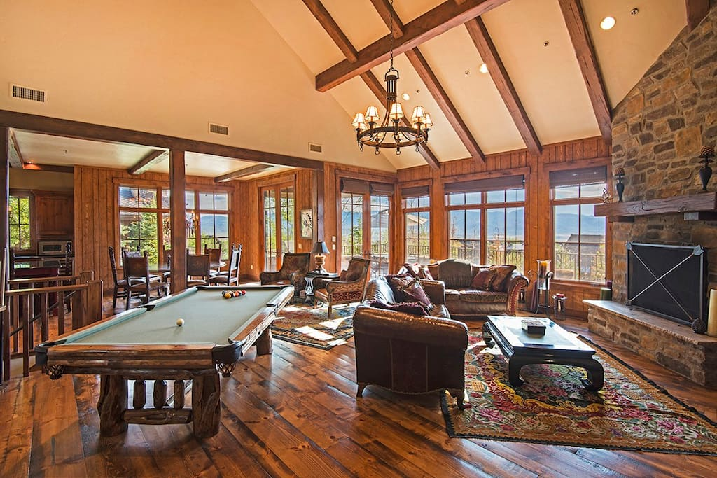 Expansive living area with vaulted, beamed ceilings, mile-high windows, a stone fireplace and various hang-out spots for your group.