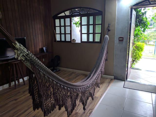 Espaço para viajantes descansarem. Fica na sala. Tem uma rede e uma cama de solteiro. Fica no primeiro andar.