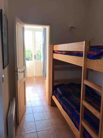 Chambre avec un lit superposé et un lavabo.
