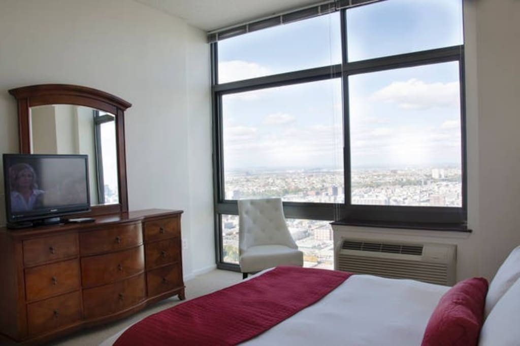 Master bedroom with dresser, flat screen TV, club chair and floor to ceiling windows providing lovely natural light and amazing views