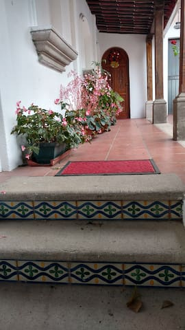 Entrance to the house trough an spanish corridor with flowers and plants that wellcome you.