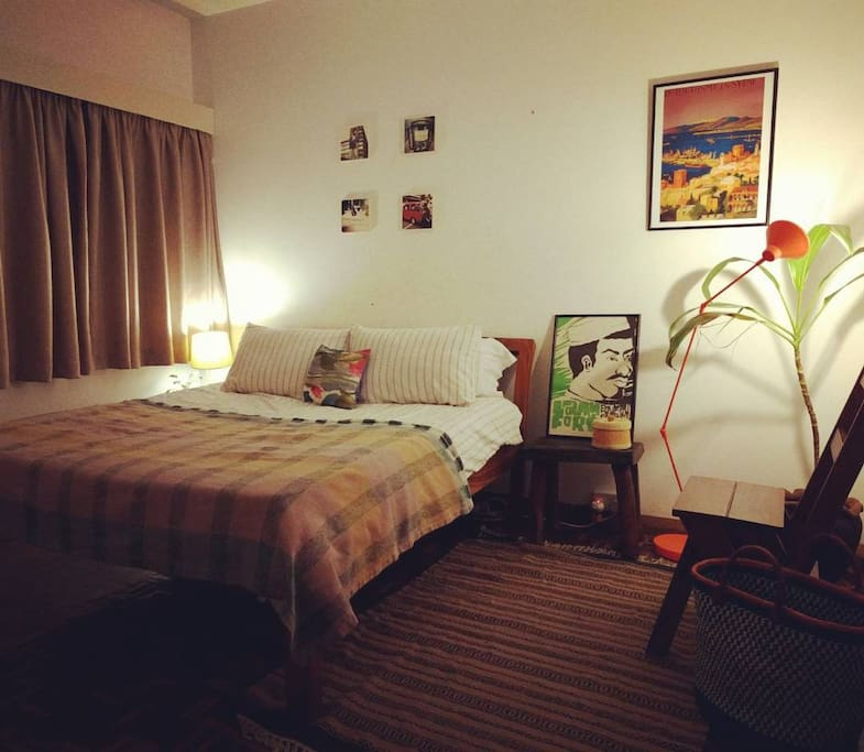 Stylish double bedroom decorated with East African art and crafts, with luxurious en suite bathroom