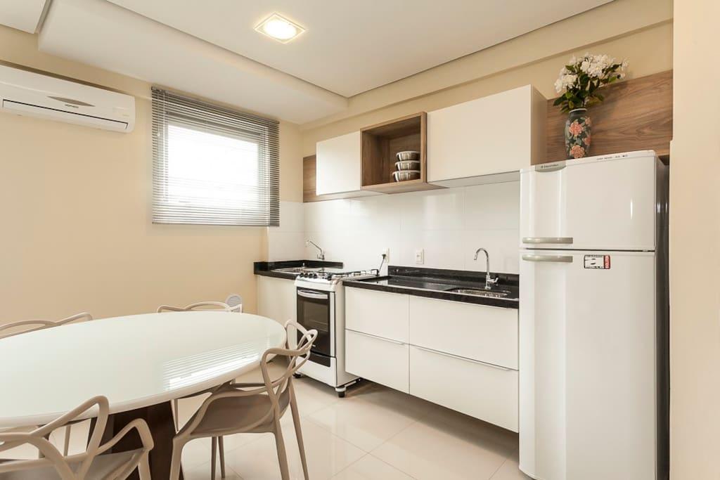 Cozinha conjugada com sofá, mesa com tampo de vidro, 4 cadeiras em polietileno, ar-condicionado e cozinha completa, painel com TV e Wi-fi. Geladeira e Fogão.