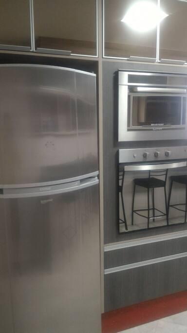 Cozinha com geladeira, forno, fogão.