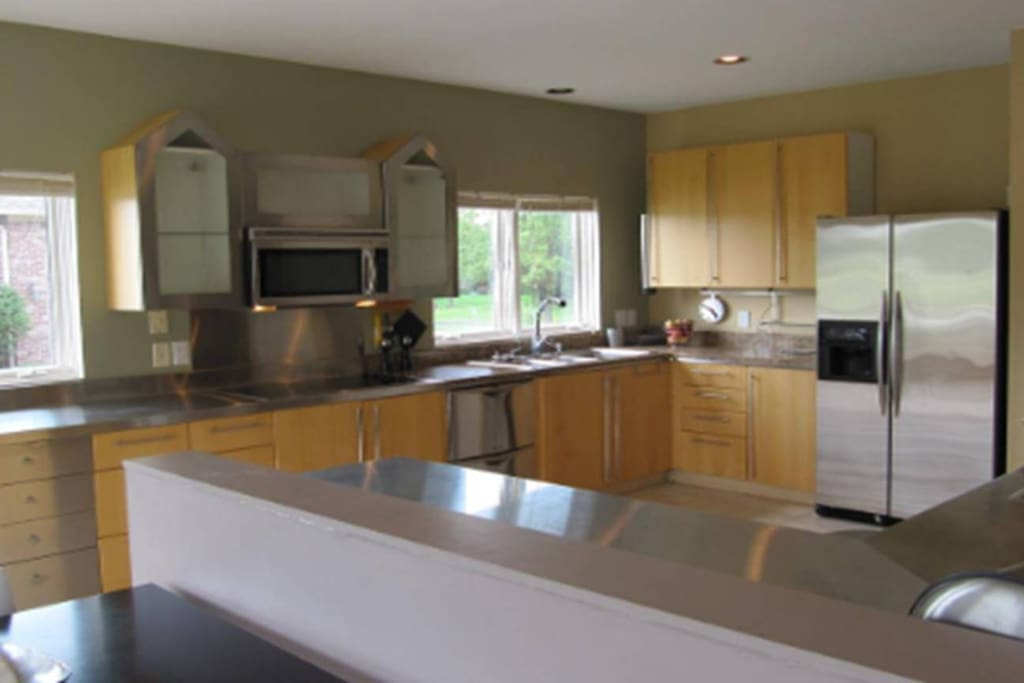 Contemporary kitchen with granite and stainless steel countertops. Enjoy the water view while you prepare breakfast or dinner with friends and family!  Or order out!  Yum!