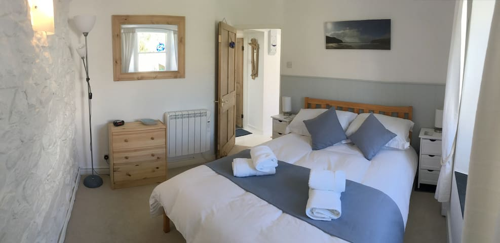 Double bedroom with original granite wall, walk-in wardrobe, chest of drawers, bed-side cabinets and lights.  Sash window over-looking decking area.