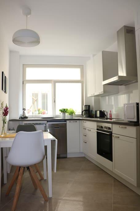 Küche mit Mikrowelle, Geschirrspülmaschine, Herd, Backofen, Kaffeemaschine, Wasserkocher und Toaster