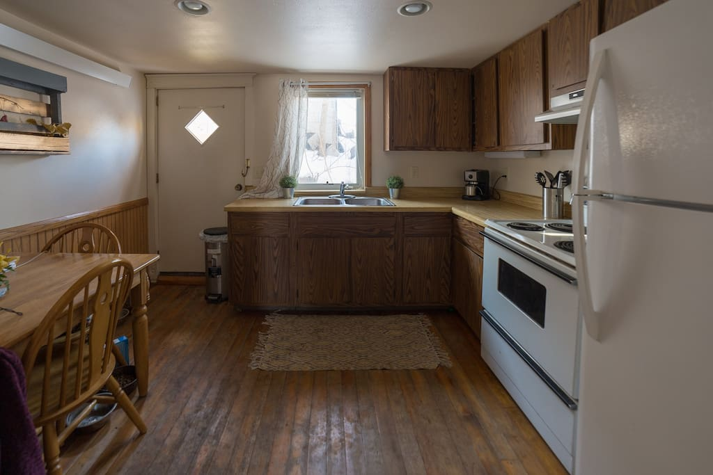 Full kitchen with table and back door