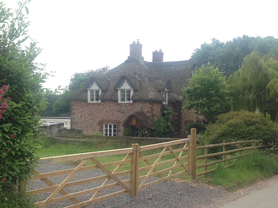 Field entrance, with cottage in the background.