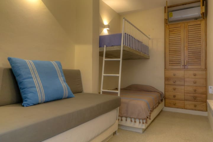 Back garden connects two of the bedrooms.  This bedroom has 1 double bed, 1 lower single and 1 upper, bunk type single bed.  All bedrooms have a/c.
