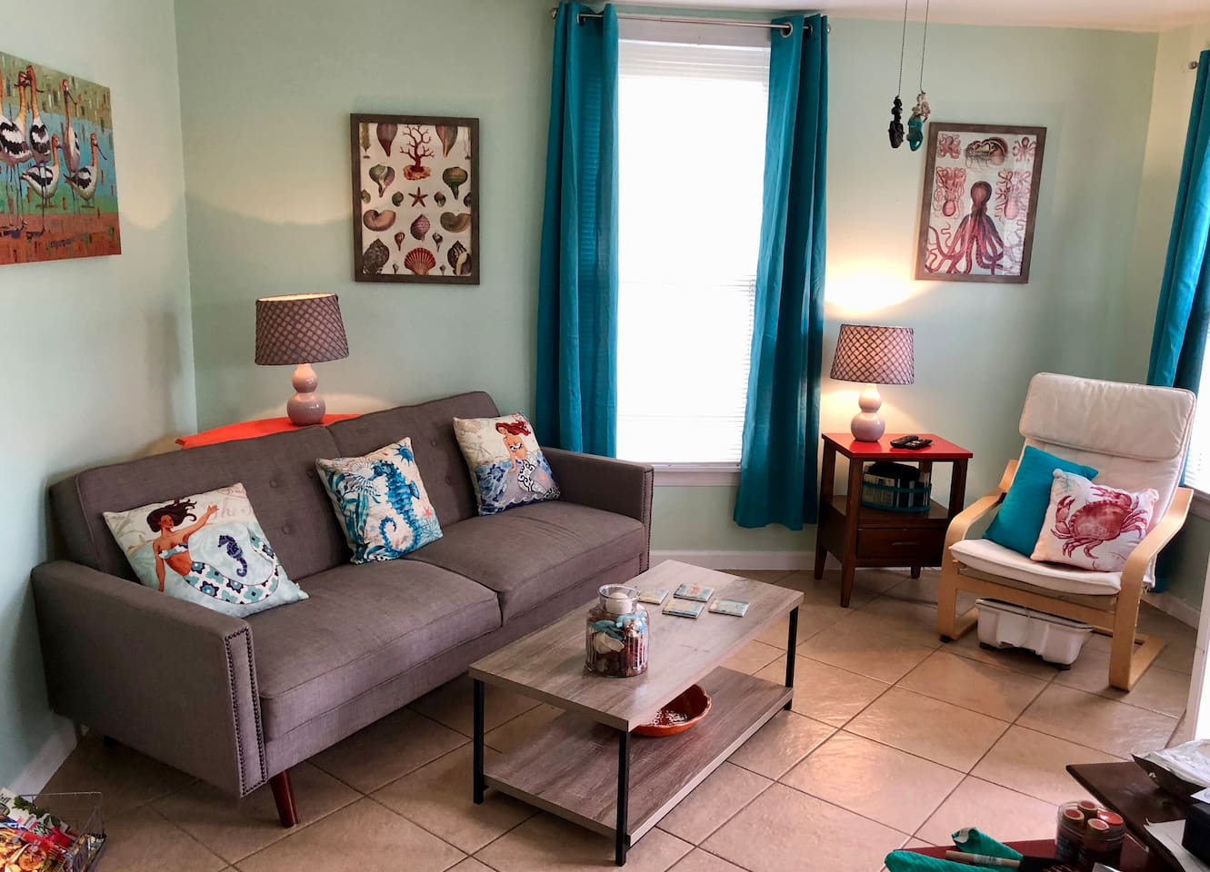 A living room to relax and enjoy with a fold down couch for guest or child to sleep on, windows to the landscaped yard and outdoor deck area