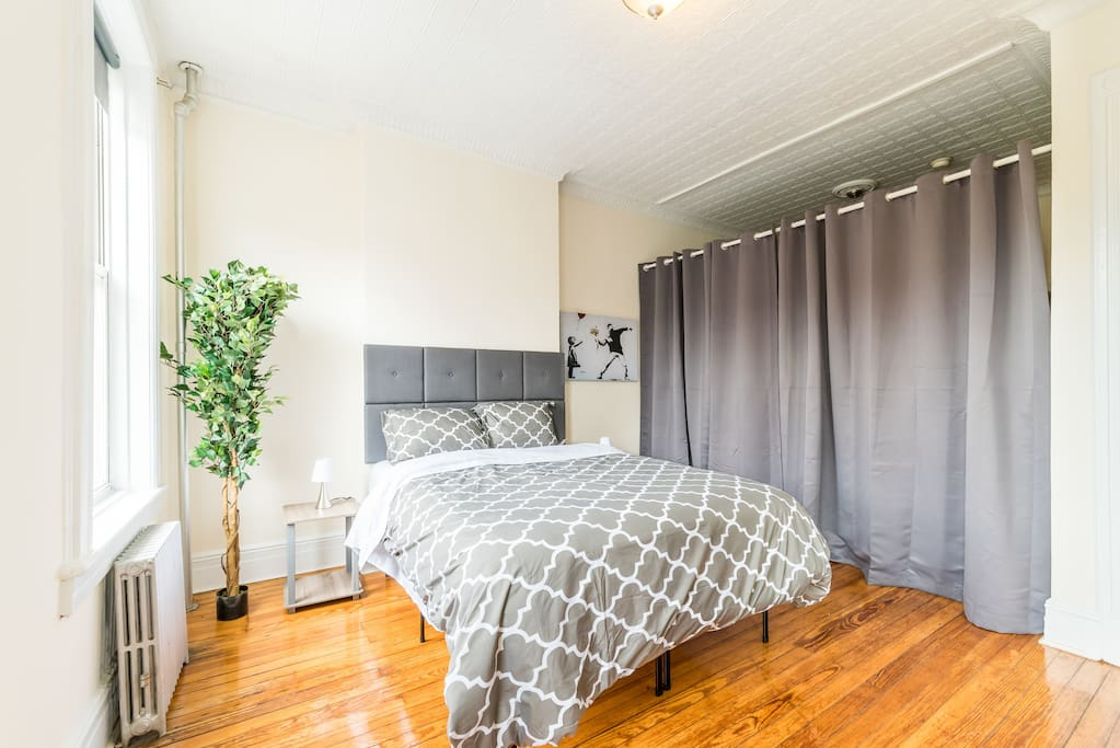Thick black out curtain separates the space into two large bedrooms. Master bedroom includes a desk and chair.