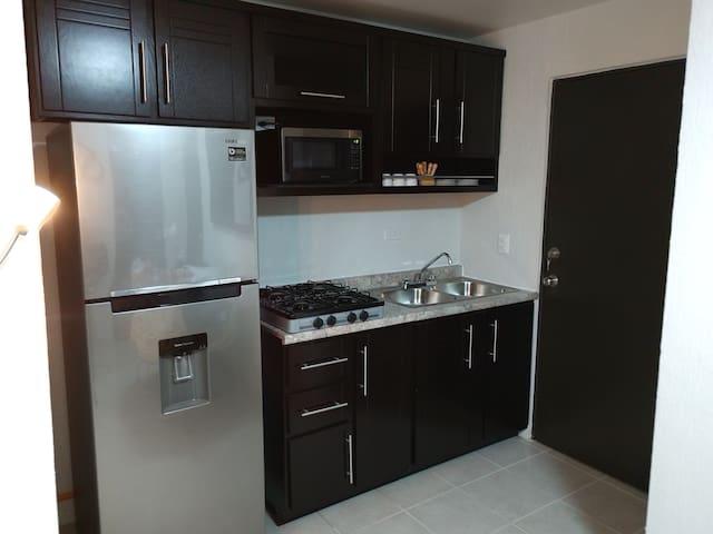 Cocina integral con parrilla para cocinar , refrigerador, horno de microondas y cafetera .