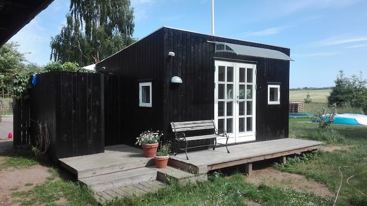 Utraditionel landlig idyl med to huse og udebad