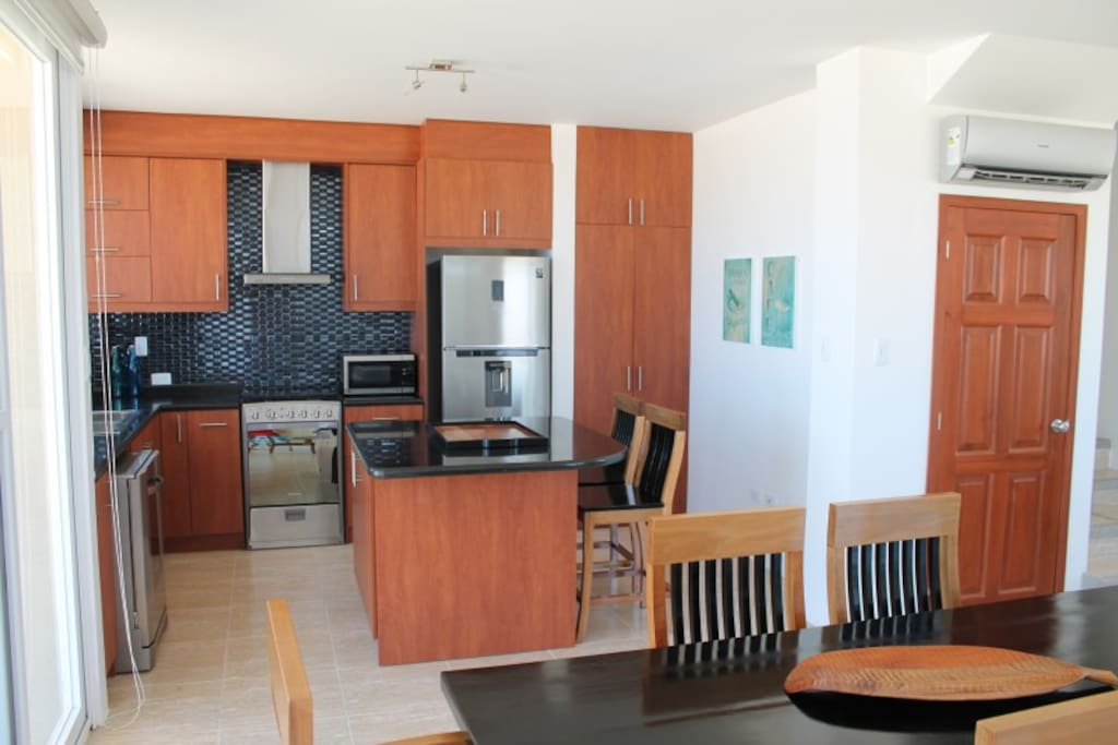 Gourmet kitchen with granite counter tops, stainless steel fridge and stove.