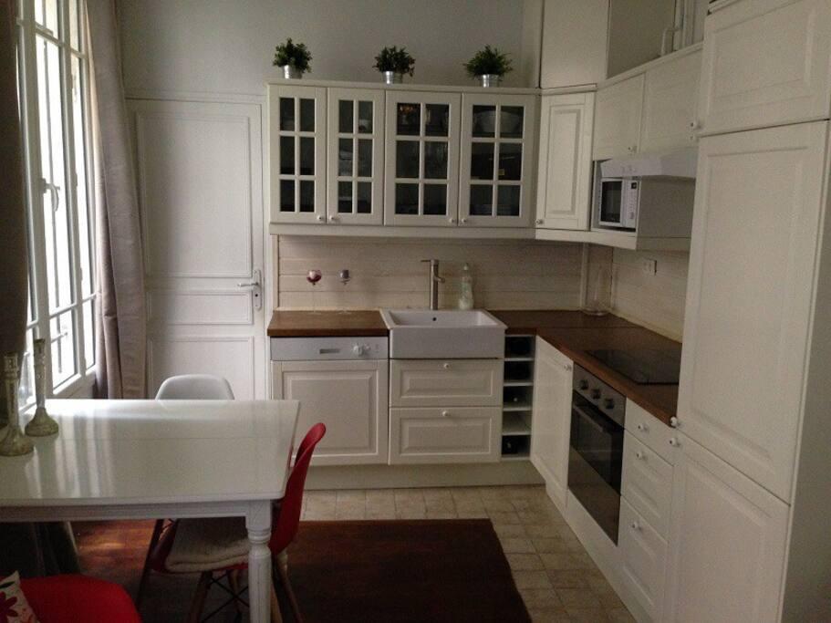 Un coin cuisine avec lave vaisselle, machine à laver le linge et Nespresso