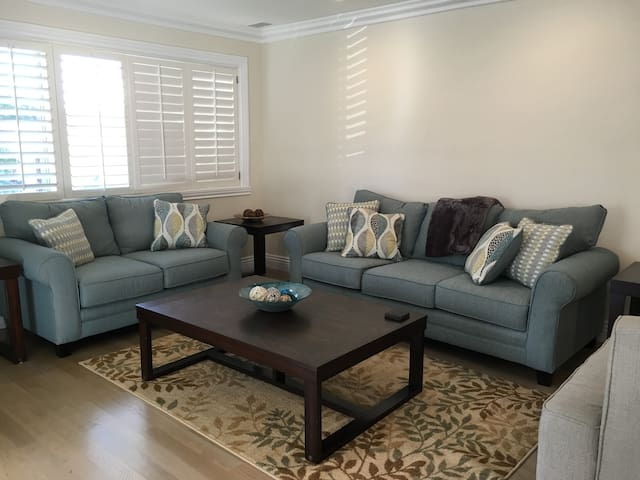 The living room is right off the entryway, and is a great place to hang out, with large couch, love seat, oversized chair, and oversized coffee table, over an attractive rug, with three end tables around the room. The hardwood floors throughout the house begin here.