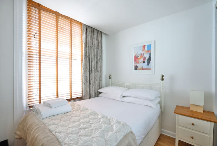 Bedroom with side table with reading lamp for more storage