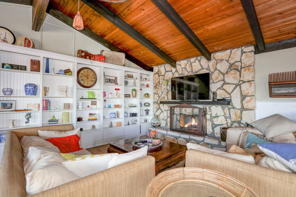 """The spacious living room in the 2BR unit provides a pair of comfy couches surrounding a 55"""" flat-screen TV with smart apps and a wood-burning fireplace."""