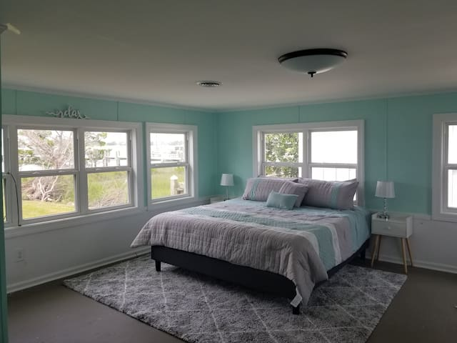This master suite features the most luxurious, indulgentking size bed surrounded by windows. To the right is the dock and ICW, to the left and across the street is the sound. It is incredible scenery! Each lamp is a 3 way touch with usb ports. Multi charger cords are in each nightstand for your convenience.