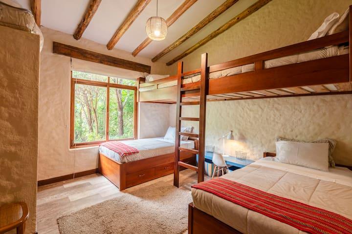 Dormitorio Petirojos: Amplia habitación con 4 camas de plaza y media cada una, con baño privado.