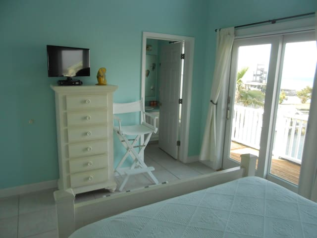 Upstairs guest bedroom with attached bath, and balcony with view of boat dock.