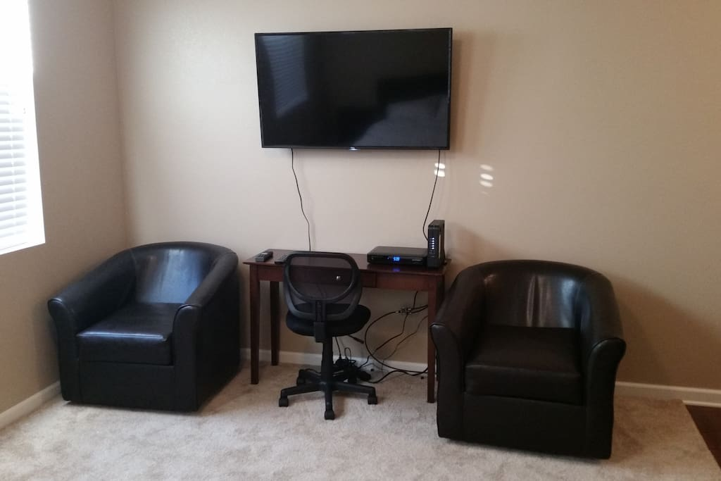 Lounge chairs, work desk with free wifi, and a 48 inch flat panel TV with cable.