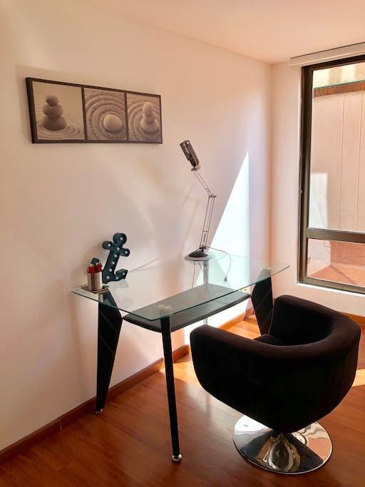 La habitación es muy luminosa y con escritorio de vidrio con patas de cuero negro, lámpara de escritorio, cuadro decorativo y silla para el escritorio. El escritorio será para tu uso privado.