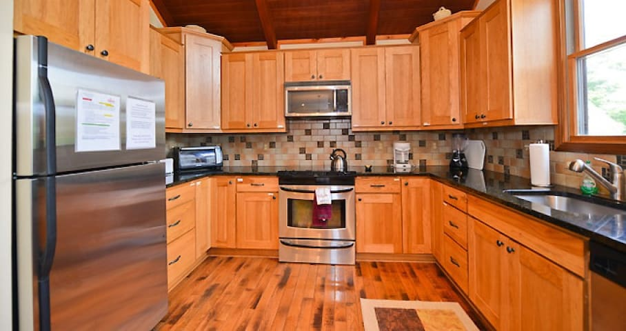 Gourmet kitchen with custom cabinetry andvfully stocked.