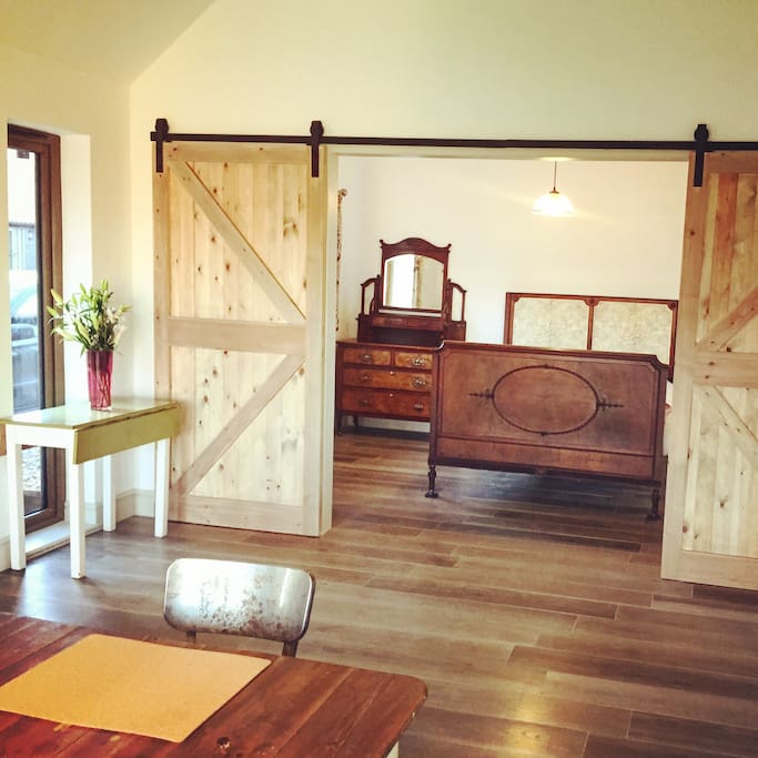 Bespoke barn doors leading into the traditional style bedroom in Barn 5 (Lily)