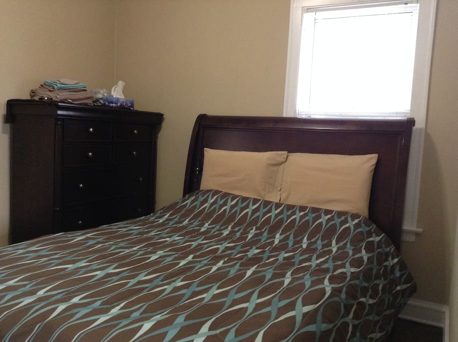 Private room with a queen size bed, large dresser, iron and board and closet.