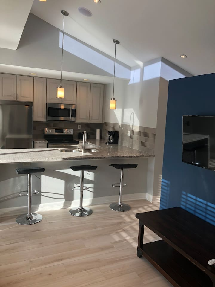Beautiful open concept kitchen, dining and living area with vaulted ceilings and lots of natural light.