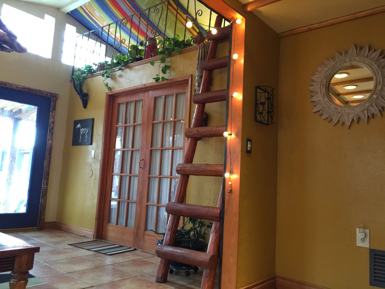The blue door leads to the back yard area, west side, where you will want to hang out and watch our awesome sunsets! The ladder leads to a more or less decorative loft, which plants love to live in.