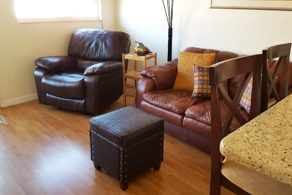 Living room area is tastefully decorated.  Wood laminate floors are installed throughout the condo with the exception of the bathroom which has tile.