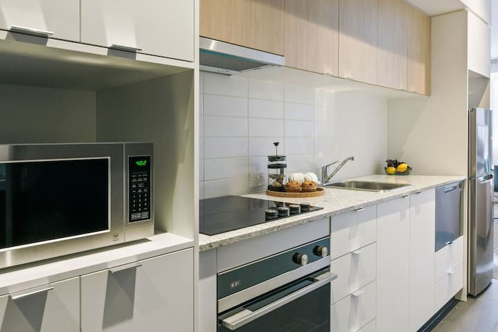 The relaxed living area contains a sofa, LCD TV with Foxtel and work desk, whilst the fully equipped kitchen provides a cooktop, oven and full-size fridge, and dining table.